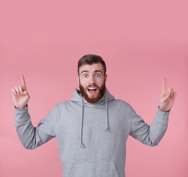 Young handsome happy amazed red bearded man in gray hoodie,stands over pink background looks at the camera with wide open mouth and eyes, wants to draw you attention and points up to copy space.