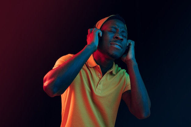 The young handsome happy hipster man listening music with headphones at black studio with neon lights. disco, night club, hip hop style, positive emotions, face expression, dancing concept