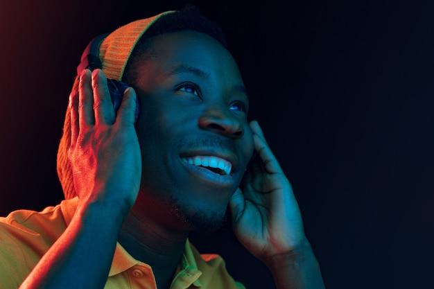 Il giovane uomo bello hipster felice ascoltando musica con le cuffie in studio nero con luci al neon. discoteca, night club, stile hip hop, emozioni positive, espressione del viso, concetto di ballo