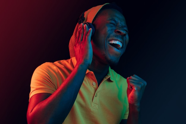 The young handsome happy hipster man listening to music with headphones at black studio with neon lights