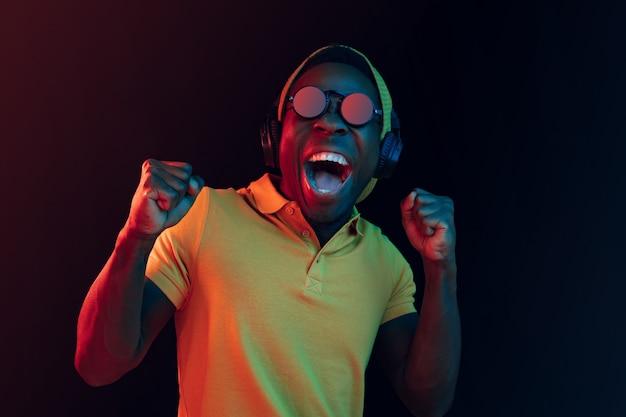 Il giovane uomo bello hipster felice che ascolta la musica con le cuffie in studio nero con luci al neon
