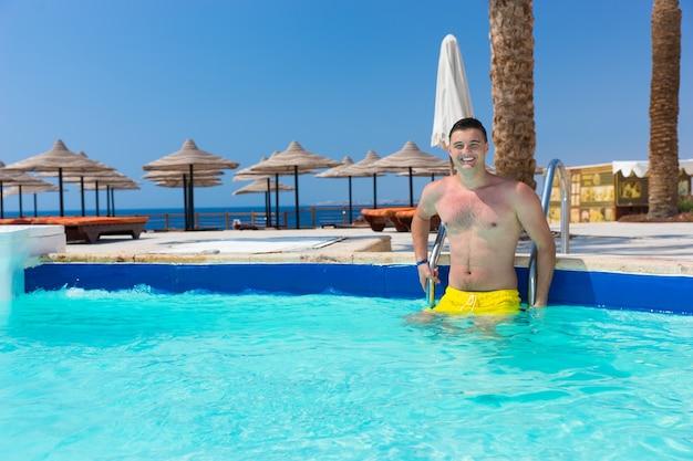 화창한 여름날 호텔 수영장에 서서 카메라를 보며 웃고 있는 젊고 잘생긴 행복한 남자