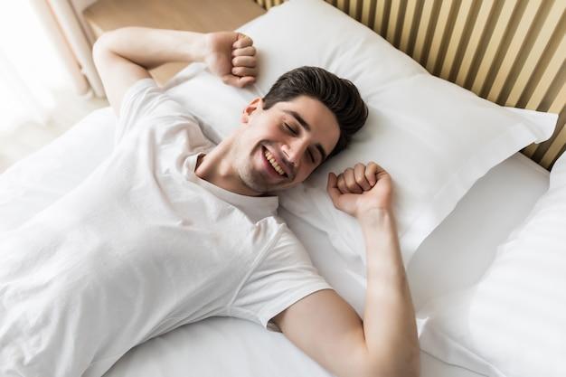 Молодой красивый счастливый человек просыпается на кровати, вид сверху