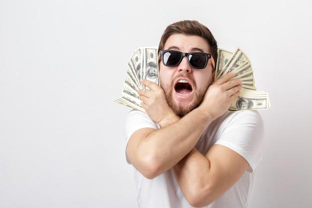Молодой красивый счастливый человек с бородой в белой рубашке держит много стодолларовых купюр. деньги