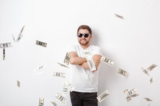 ドル紙幣のお金の雨の下に立っている白いシャツのひげを持つ若いハンサムな幸せな男
