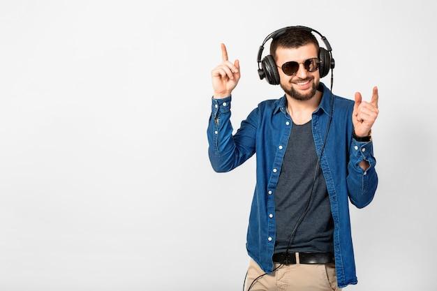 Молодой красивый счастливый улыбающийся человек танцует и слушает музыку в наушниках на белом фоне студии, в джинсовой рубашке и солнцезащитных очках