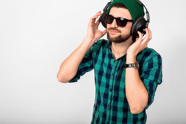 Giovane uomo sorridente felice bello che ascolta la musica in cuffie isolate su sfondo bianco studio, indossa camicia e occhiali da sole
