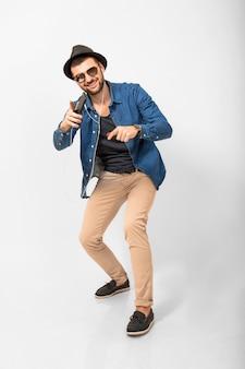 Молодой красивый счастливый улыбающийся человек, слушающий музыку в наушниках, изолированные на белом фоне студии, держа смартфон, одетый в джинсовую рубашку, шляпу и солнцезащитные очки