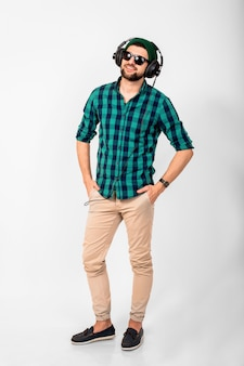 Молодой красивый счастливый улыбающийся человек, слушающий музыку в наушниках, изолированные на белом фоне студии, в рубашке и солнцезащитных очках