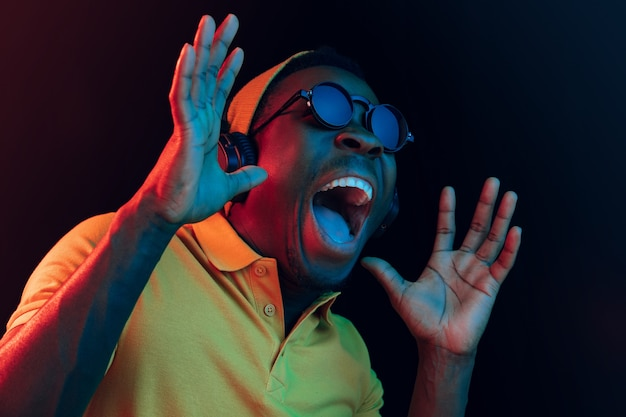 The young handsome happy surprised hipster man listening music with headphones at black studio with neon lights. disco, night club, hip hop style, positive emotions, face expression, dancing concept