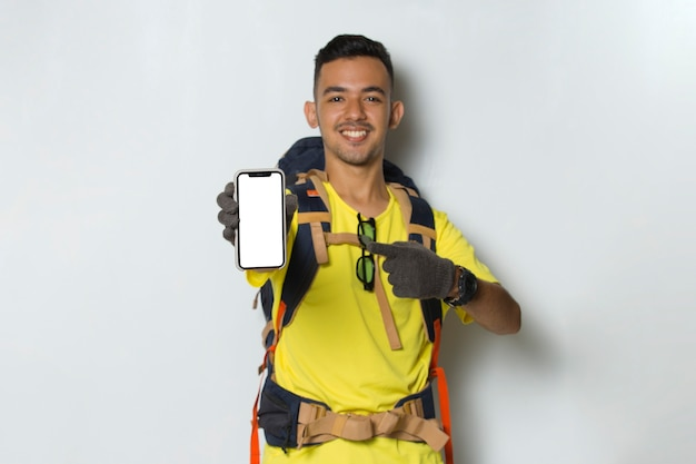 Young handsome hiker man hold mobile phone with blank empty screen isolated on white background