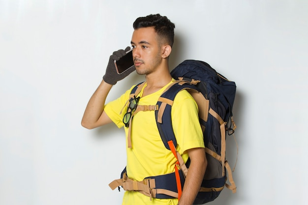 Young handsome hiker man using mobile phone isolated on white background