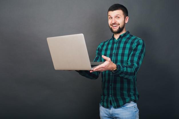 Молодой красивый битник бородатый мужчина держит ноутбук в руках, зеленая клетчатая рубашка, положительные эмоции, счастливый, улыбающийся, удивление, серый фон