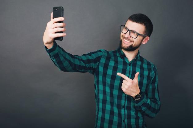 若いハンサムな流行に敏感なひげを生やした男の手でスマートフォンを保持している、緑の市松模様のシャツ、肯定的な感情、幸せ、笑顔、灰色の背景