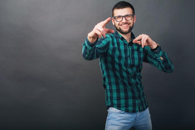 灰色の背景、緑の市松模様のシャツ、眼鏡、人差し指、幸せ、笑顔、前向きな感情の若いハンサムなヒップスターのひげを生やした男