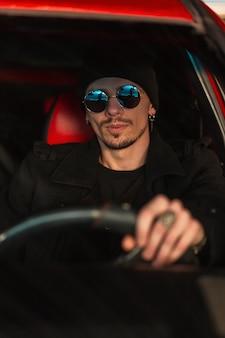 멋진 선글라스를 쓴 모자와 패션 코트를 입은 젊고 잘생긴 힙스터 남자가 차를 운전하고 있다