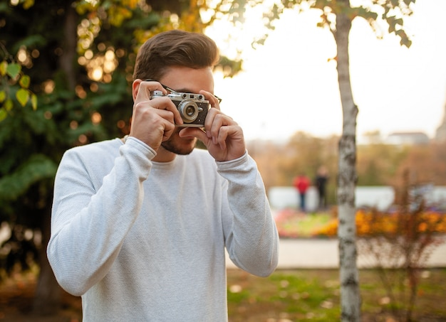 Young handsome hipster guy walks in a beautiful autumn park