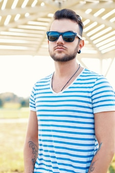 Young handsome hipster guy with beard in a stylish t-shirt and sunglasses in a sunny summer day at the beach.