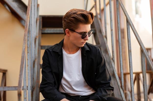 우아한 검은 셔츠에 유행 헤어 스타일과 유행 선글라스에 젊은 잘 생긴 소식통