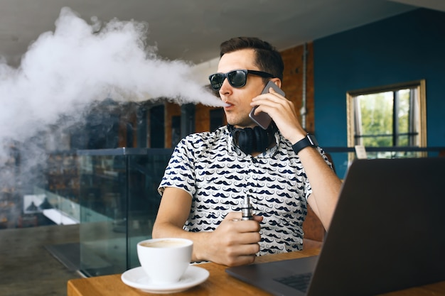 Young handsome hipster man insunglasse sitting in cafe with a cup of coffee, vaping and releases a cloud of vapor.