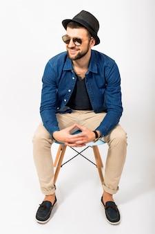若いハンサムな流行に敏感な男、孤立した白いスタジオ背景、スタイリッシュな服、デニムシャツ、ズボン、帽子、サングラス、椅子に座って、一緒に手、ポーズ、笑顔、幸せ、肯定的