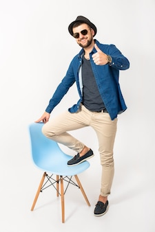 Young handsome hipster man, isolated white studio background, stylish outfit, denim shirt, trousers, hat, sunglasses, standing on chair, cheerful, happy, smiling, positive, success, cheerful, thumb up