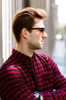 通りでポーズをとる若いハンサムな流行に敏感な男、ビジネスマン、格子縞のシャツサングラス、ヨーロッパの市内中心部。