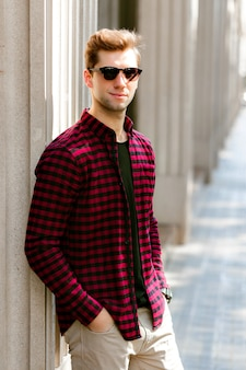 Young handsome hipster man posing in the street, it businessman, plaid shirt sunglasses, europe city center.