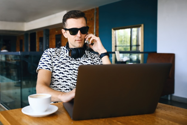 Young handsome hipster man in sunglasses is using laptop, talking mobile phone in cafeteria.