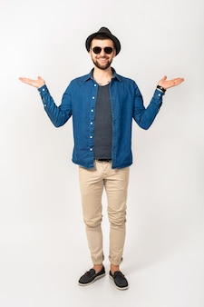 Young handsome hipster man, trendy style outfit, denim shirt, trousers, sunglasses, hat, happy, smiling, positive emotion, isolated, empty hands up, compare