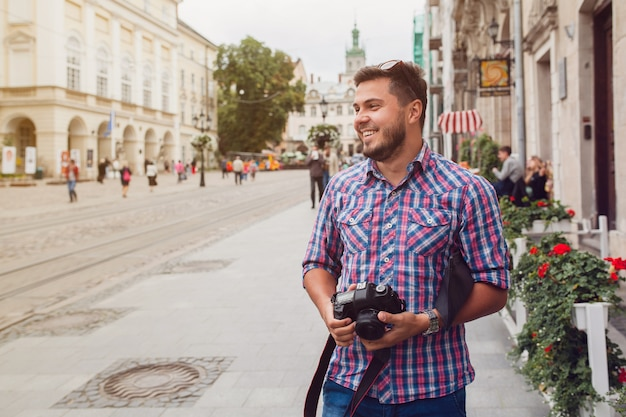 旧市街の通りを写真カメラで歩く若いハンサムな流行に敏感な男