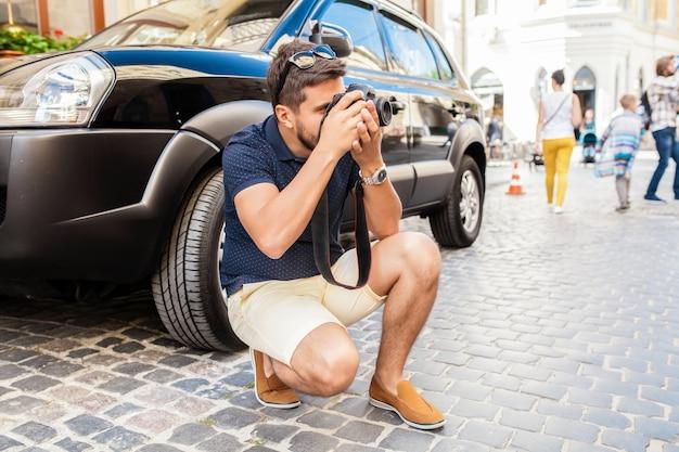 Битник молодой красивый мужчина идет с фотоаппаратом на улице старого города