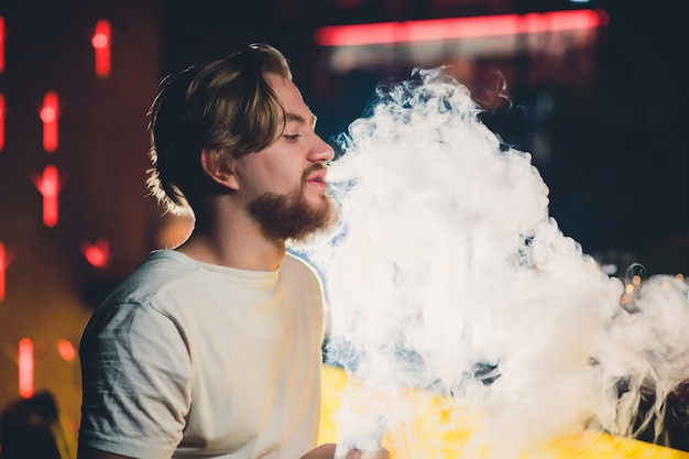 Young handsome hipster man with beard sitting in cafe with a cup of coffee, vaping and releases a cloud of vapor.