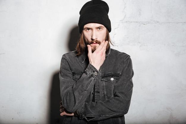 Молодой красивый хипстер с бородой и усами, глядя на фронт изолирован на стене