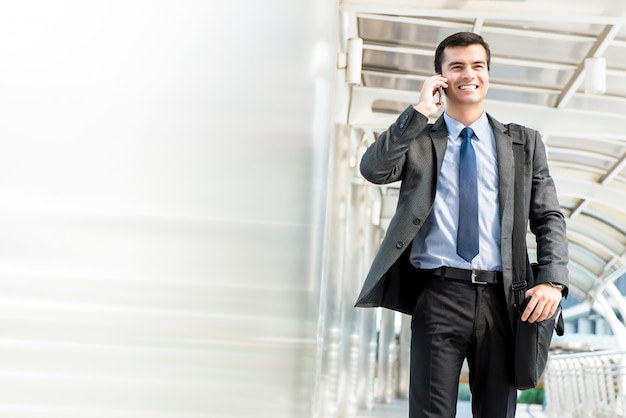 Young handsome hispanic businessman walking and calling on mobile phone