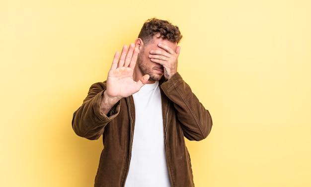 젊고 잘생긴 히스패닉 남자는 손으로 얼굴을 가리고 다른 손을 앞으로 올려 카메라를 멈추고 사진이나 사진을 거부합니다.