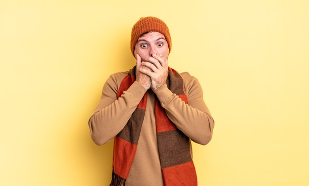Young handsome hispanic man covering mouth with hands with a shocked, surprised expression, keeping a secret or saying oops