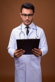 Young handsome hispanic man doctor against brown background