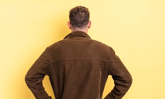 젊고 잘 생긴 히스패닉 남자는 혼란스럽거나 가득 차거나 의심과 질문을 느끼고, 엉덩이에 손을 얹고, 후면을 봅니다.