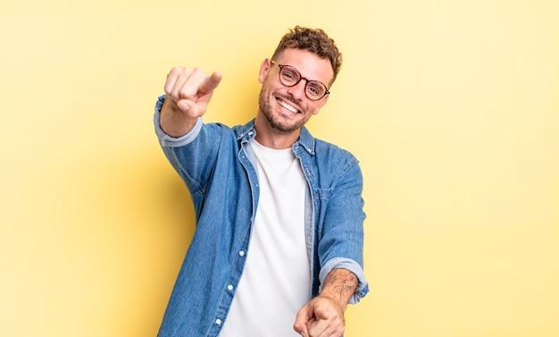 Молодой красивый латиноамериканец чувствует себя счастливым и уверенным, указывая на камеру обеими руками и смеясь, выбирая вас