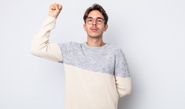 Young handsome hispanic man feeling serious, strong and rebellious, raising fist up, protesting or fighting for revolution