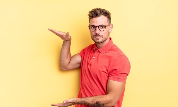 측면 복사 공간에 양손으로 물건을 들고 물건을 보여주거나 제공하거나 광고하는 젊고 잘생긴 히스패닉 남자