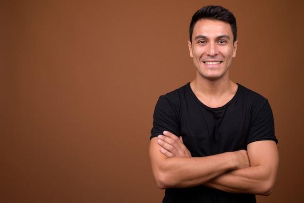 茶色の壁に若いハンサムなヒスパニック系男性