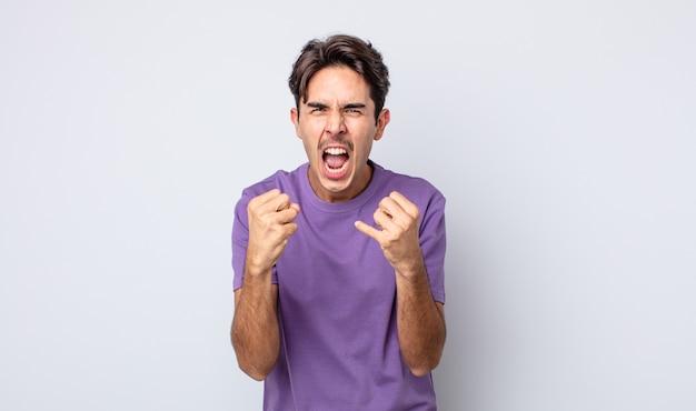 Молодой красивый латиноамериканский мужчина агрессивно кричит с раздраженным, разочарованным, злым взглядом и сжатыми кулаками, чувствуя ярость