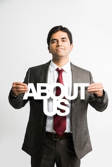 Young and handsome indian asian businessman holding a banner or board in which different words is written by paper cutting in white colour, standing isolated over white background