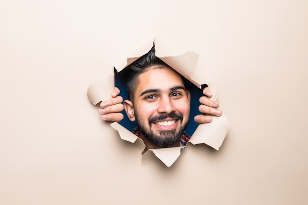 Young handsome indian bearded man smile look from beige paper hole
