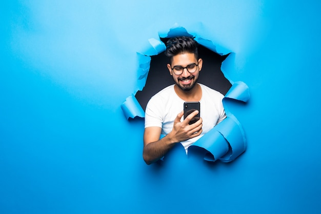 Young handsome indian bearded man typing phone look from blue paper hole