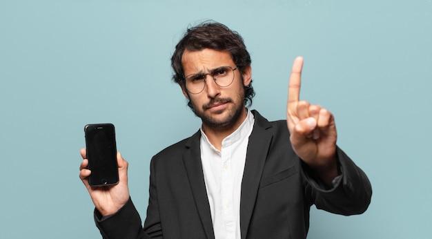 彼の電話の空の画面を示す若いハンサムなインドのビジネスマン