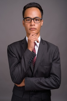 Young handsome indian businessman against gray wall