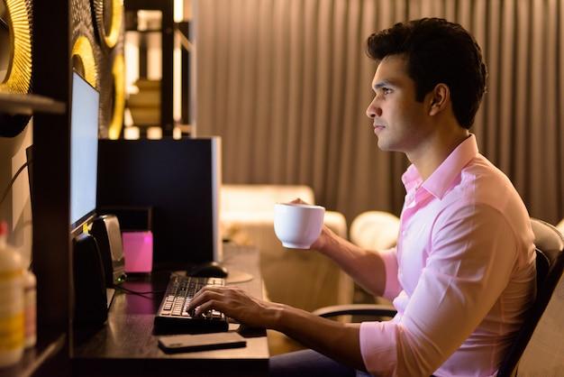 Молодой красивый индийский бизнесмен пьет кофе, работая сверхурочно дома